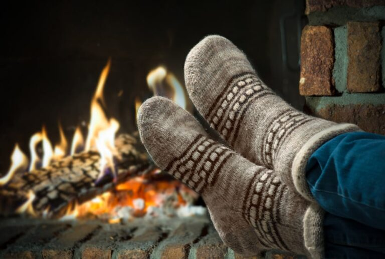 Close-up-of-feet-in-cozy-socks-in-front-of-fireplace