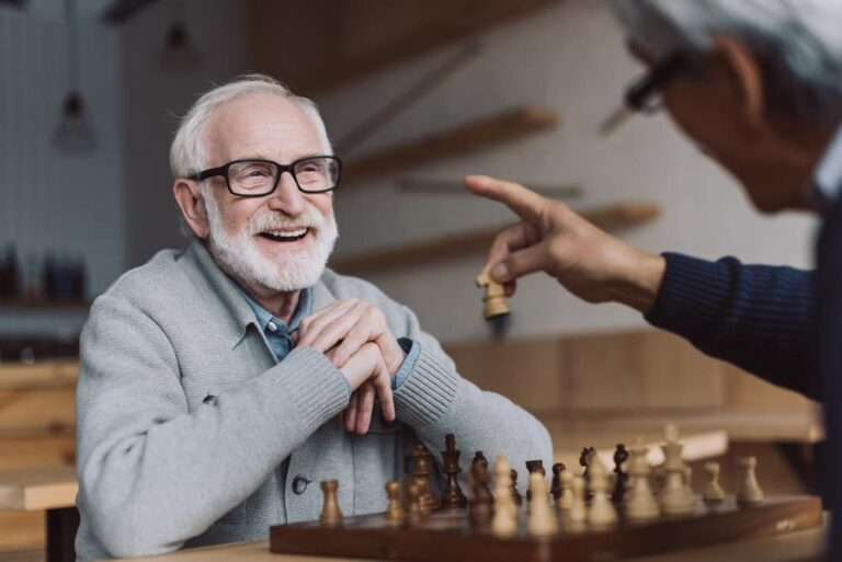 Senior-man-smiling-while-playing-chess-with-friend
