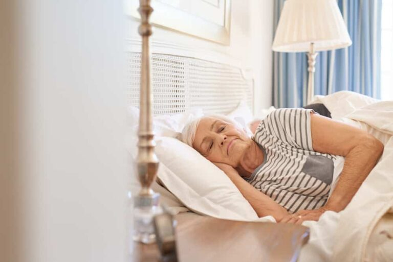 Senior-woman-lying-in-bed-with-eyes-closed