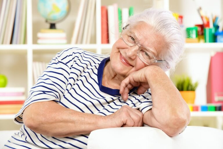 Senior-woman-on-couch-smiling-head-cocked-to-the-side