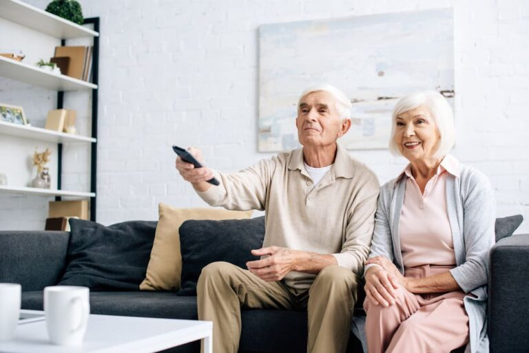 Smiling-senior-couple-on-couch-holding-remote