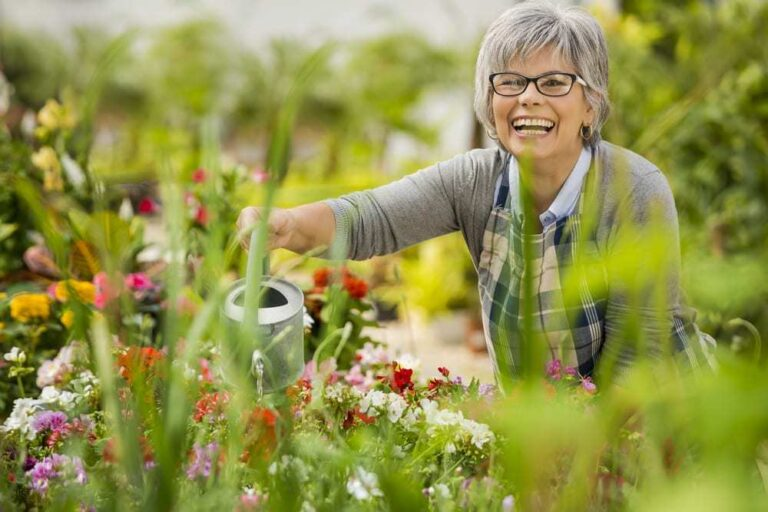 Smiling-senior-woman-watering-flowers-in-a-lush-garden