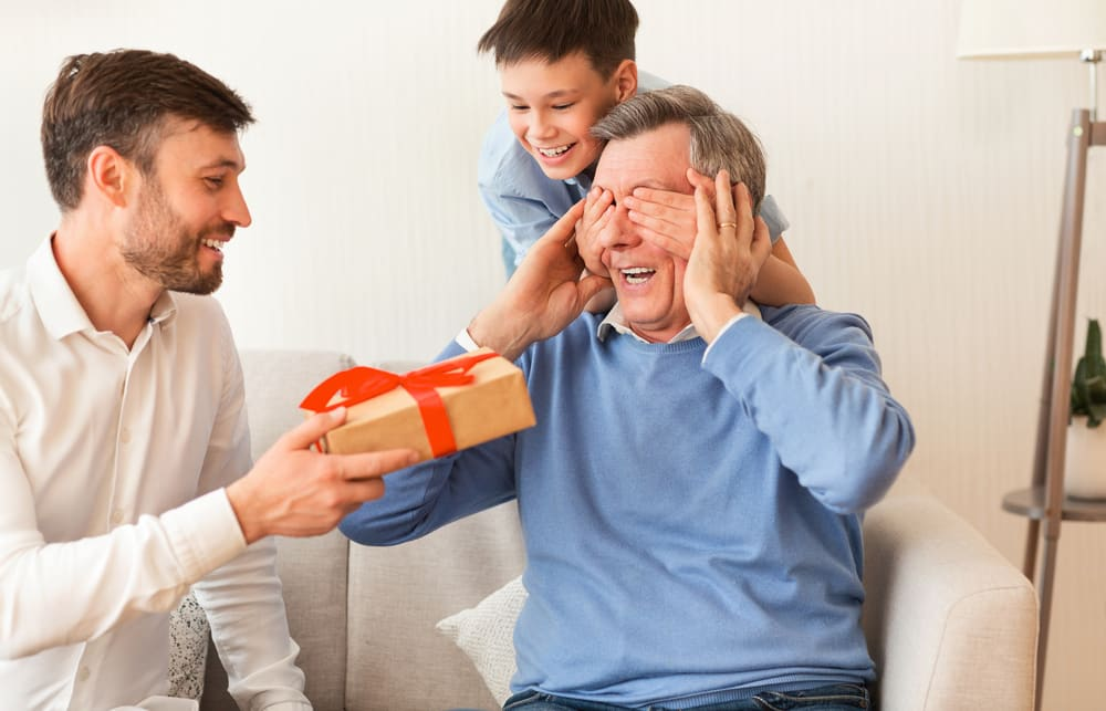 Man giving gift to senior man, whose eyes are covered by smiling boy