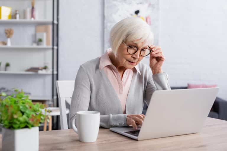 Senior woman looking at laptop while seated at desk