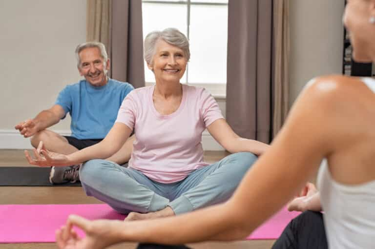 Smiling senior man and woman in yoga class, following young instructor