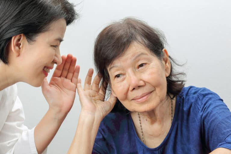 Smiling young woman whispering into the ear of senior woman